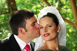 bride and groom kiss on cheek
